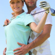 A woman with a golf club and a man putting his hands on her waist — Stock Photo
