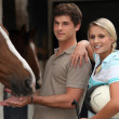 Stock Photo: Young couple at riding stable
