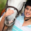Stock Photo: Young womcaressing her horse