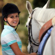 Young woman taking care of her horse — Stock Photo