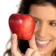 Foto Stock: Young woman holding an apple