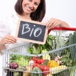 Woman with a trolley of organic vegetables - Stock Photo
