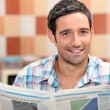 Stock Photo: Man reading a newspaper in the kitchen