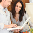 Couple using a laptop in the kitchen — Stock Photo