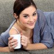 Woman laying on sofa with mug of coffee - Stock Photo