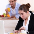 Stock Photo: Career womeating breakfast while working
