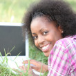 Stock Photo: Womusing laptop in grass
