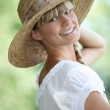Woman smiling with straw hat — Stock Photo