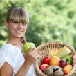 Woman holding a basket of fruit — Stock Photo