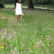 Stock Photo: Summery womwalking through pretty wild flower meadow