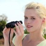 Woman holding binoculars — Stock Photo #7716373