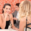 Two girls dressed in robes talking in a restaurant — Stock Photo