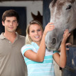 Young couple stood by horse — Stock Photo