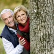 Couple hiding behind tree — Stock Photo