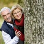 Couple hiding behind tree — Stock Photo