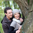 Couple stood by tree - Stock Photo