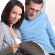 Stock Photo: Mature couple skimming through catalogue