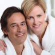 Smiling mature couple in bathrobes - Stockfoto