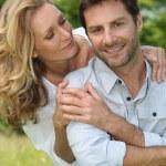 szczęśliwa para siedział na zewnątrz dotykania rękami — Zdjęcie stockowe