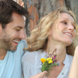 Stock Photo: Husband offering wife flowers