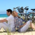 Couple on the beach with bikes — Stock Photo
