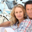 Stock Photo: Happy couple sitting by beach with their bikes