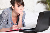 Young woman working at a laptop at home — Stock Photo