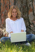 Woman on laptop under tree — Stock Photo