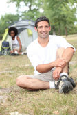 A man seated, behind him, a canvas tent and a woman — Stock Photo