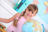 Pupil standing behind a globe — Stock Photo
