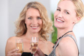 Two women with champagne flutes — Photo