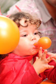 Child blowing up a balloon — Stock Photo