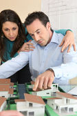 Architect and assistant gathered around model housing — Stock Photo