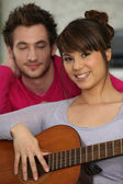 Smiling brunette playing the guitar under boyfriend's watchful eye — Stock Photo