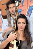 Young woman and man playing in a music band — Stock Photo
