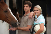 Young couple at a riding stable — Stock Photo