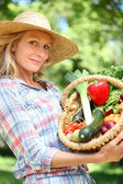 Woman with a straw hat holding basket of vegetables. — Stock Photo