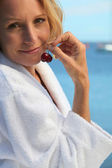 50 years old blonde woman dressed in bathrobe in front of the sea taking ch — Stockfoto