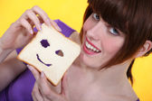 Young woman making a face in her slice of bread — Stock Photo