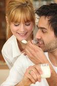 Mann, die fütterung eines esslöffel joghurt mit seiner freundin — Stockfoto