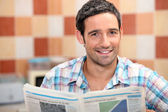 Man reading a newspaper in the kitchen — Stock Photo
