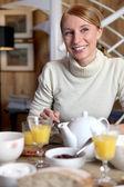 Kvinna äter frukost vid bord — Stockfoto