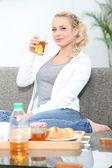 Woman on a sofa having breakfast — Stock Photo