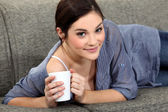 Woman laying on sofa with mug of coffee — Stock Photo
