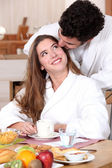Couple wearing matching bathing robes in kitchen — Stock Photo