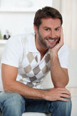 Smiling man relaxing at home — Stock Photo