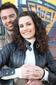 Couple standing in front wall — Stock Photo