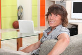 Young man sitting in a recreation room at college — Stock Photo
