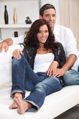 Young couple sat on couch at home — Foto Stock