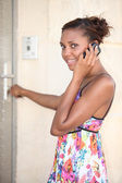 Black woman wearing a summer dress coming home and calling — Stock Photo